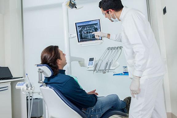 dentista aponta imagem de radiologia odontológica digital para paciente sentado na cadeira