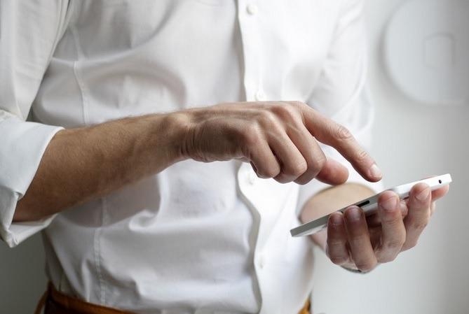 homem de camisa branca mexendo no celular