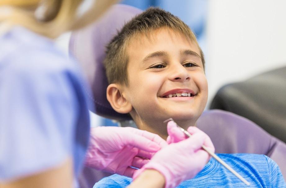 criança sentada sorri na cadeira de um consultório odontológico